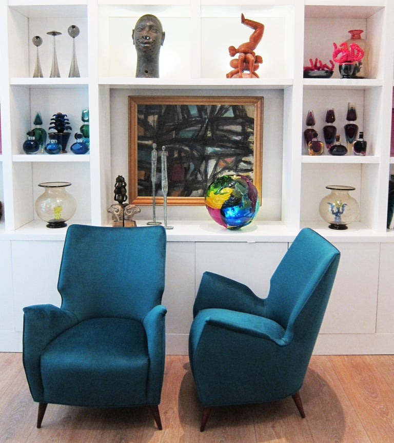 Pair of low lounge chairs in the manner of Gio Ponti.  These curvaceous club chairs seats low and are newly upholstered with a peacock blue velvet (Caspian blue) Original walnut finish conical wooden legs. Italy, circa 1950.  Restored to perfection