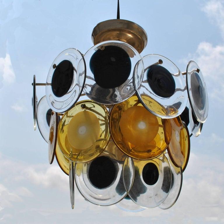 Mid-Century Modern Italian Murano Vistosi glass disc chandelier circa 1970s   24 hanging alternating amber and black glass disks on chrome base. A great example of midcentury Italian glass art.