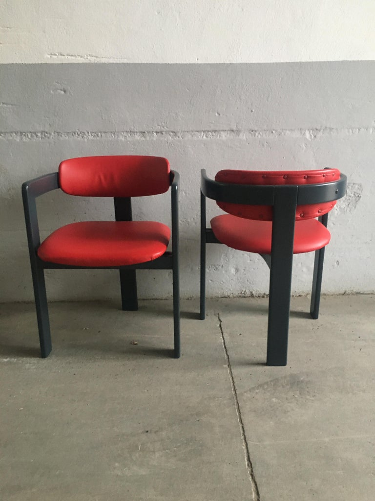 Mid-Century Modern Italian pair of red faux leather chairs in the style of Augusto Savini with dark grey lacquered wood structure. These chairs have never been used and they are in perfect vintage conditions.