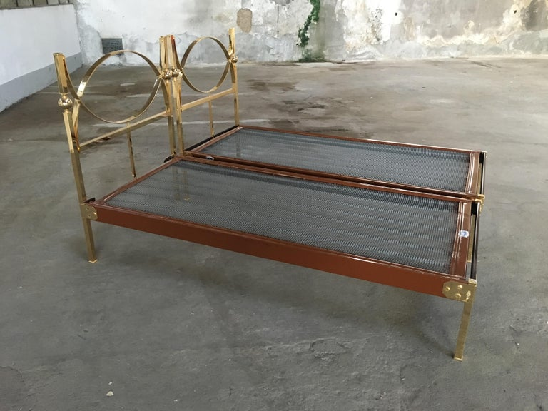 Mid-Century Modern pair of Italian single beds with gilt headboard and feet.  The beds need a mattress of cm. 80 x 190.  One of the bed misses a short bar under the headboard. In case of sell a brand new one will be provided.