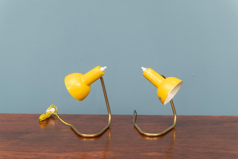 Mid-Century Modern Italian bedside or table lamps in yellow enamel with brass hairpin bases, perfect for smaller spaces. They will require new wiring for US standards.