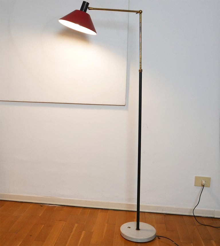 Adjustable floor lamp edited by Stilux in 1950s  Thanks to the brass arm and the little handle it s possible to change the arm position. The red reflector is adjustable too. The brass switch is on the white marble base.