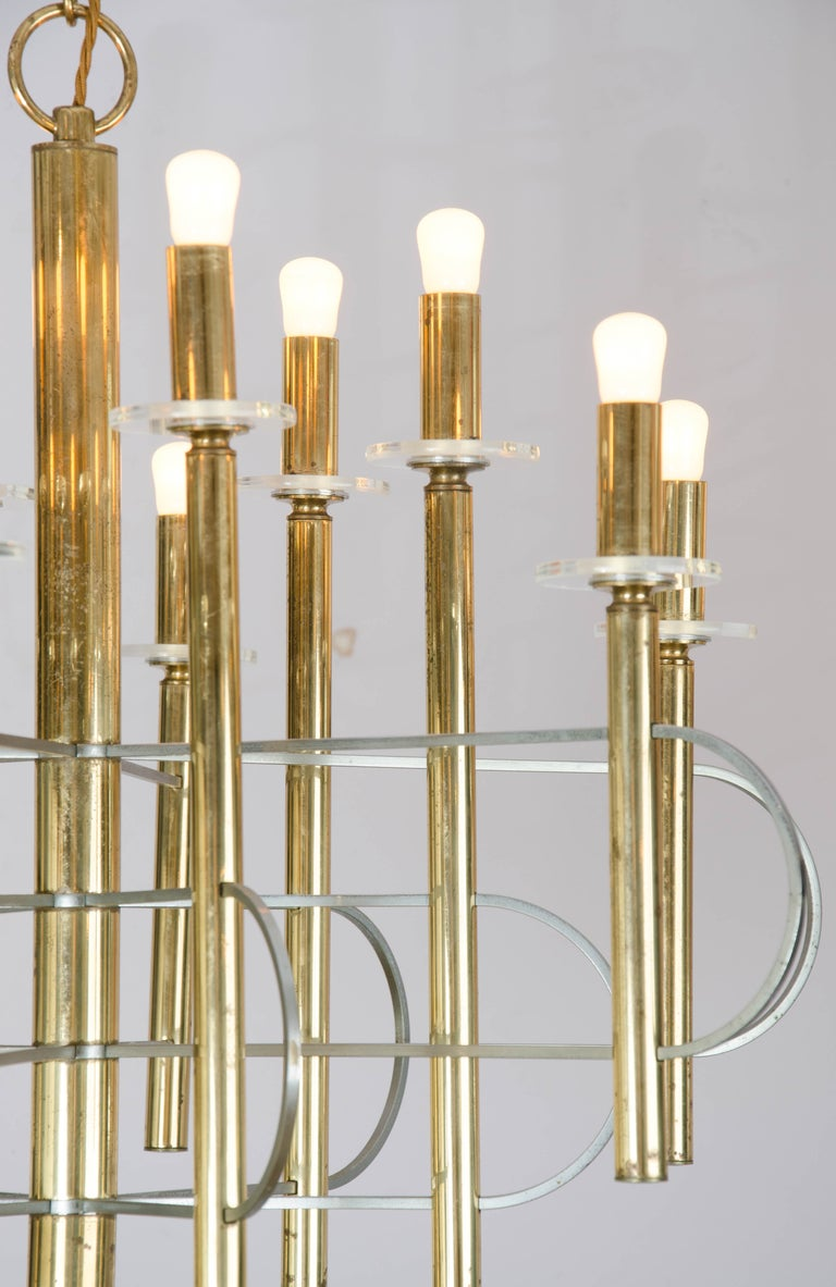 Sculptural Space Age chandelier with clean lines in brass and nickel with clear glass disks displaying 12 lights by Gaetano Sciolari, Italy.  The maximum drop is 100 cm and the chandelier height is 54 cm. Possible light bulbs, candle, golf or
