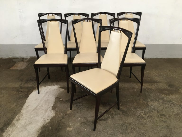 Mid-Century Modern set of 8 Osvaldo Borsani mahogany and faux leather Italian dining chairs with brass details.  The chairs are a part of a complete dining room set as shown in the photos.