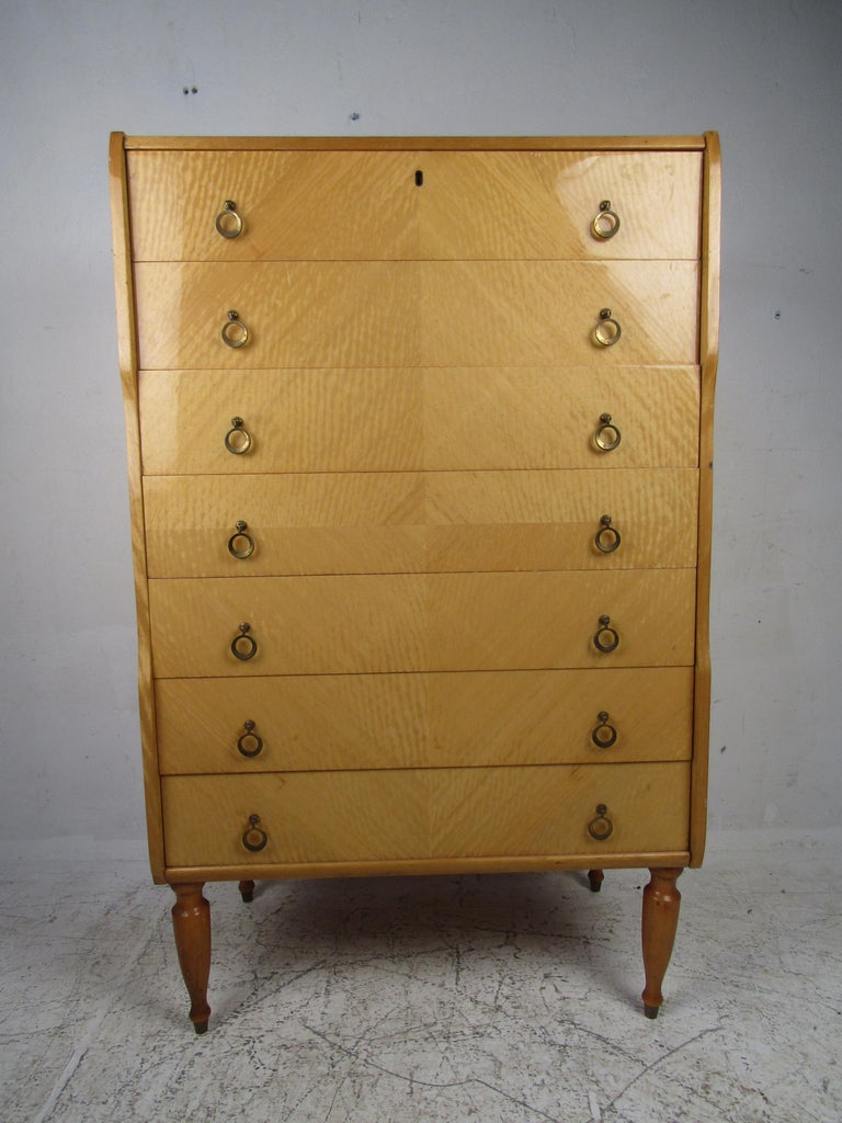 Beautiful Italian modern highboy with seven hefty drawers, ensuring plenty of room for storage. The unique circular brass pulls, sculpted legs, and blonde lacquered finish adds style and grace to any modern interior. Please confirm the item location