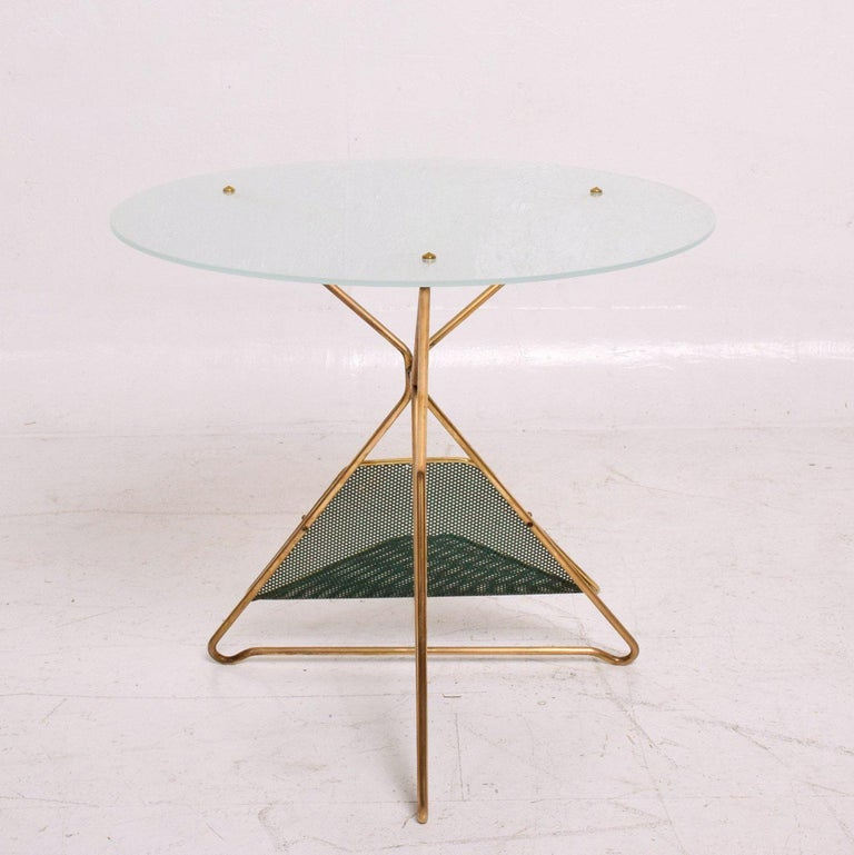 For your consideration a vintage Mid-Century Modern round table constructed with sculptural brass base and frosted round glass top. The base has a perforated metal (painted in green with brass trim) magazine holder.  Beautiful unique design.