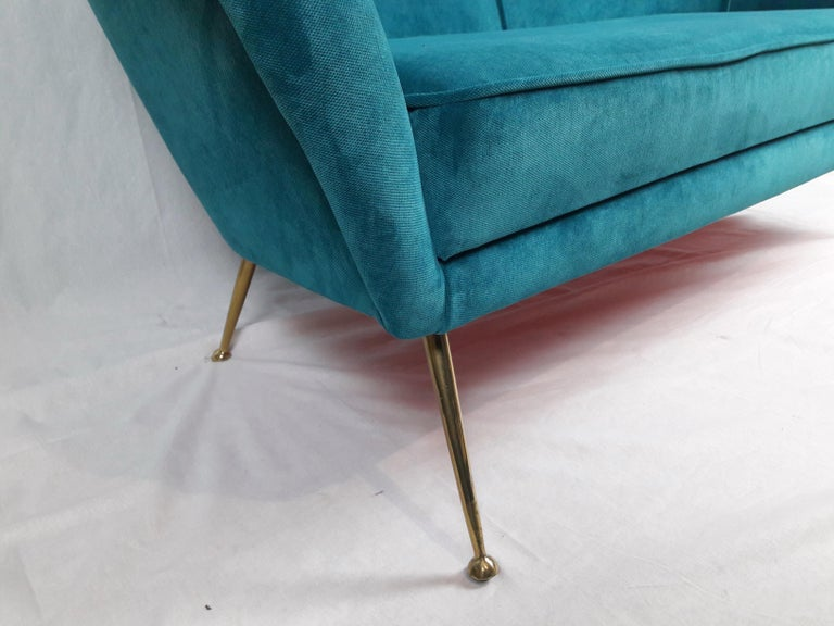 Enchanting two-seat Italian 1950s sofa characterized by typical brass 'stiletto' legs, curved line back and armrests. Reupholstered in new turquoise velvet fabric.