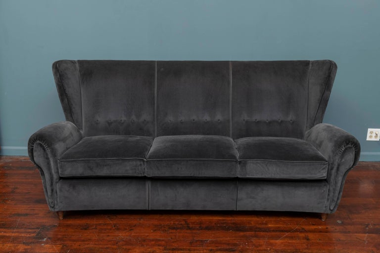 Mid-Century Modern Italian wingback sofa, upholstered in charcoal mohair with black leather piping. Completely restored and ready to install, very comfortable.