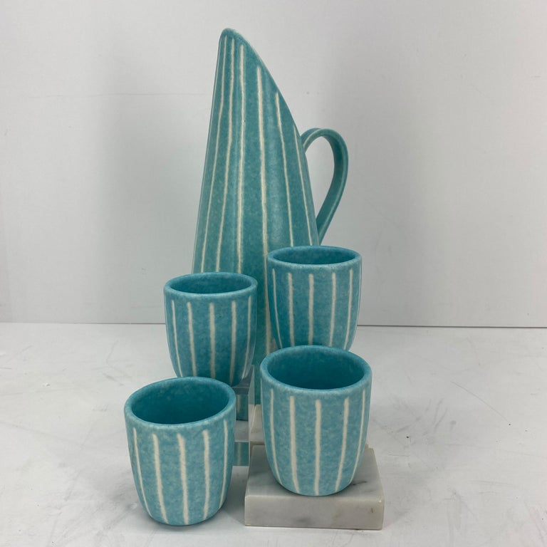 Iconic Mid-Century Modern from Southern California design. Rare and in very good condition, with its bright turquoise and creamy stripes, this beverage set, pitcher and 4 cups/beakers by Jaru of California, will make every cocktail hour even