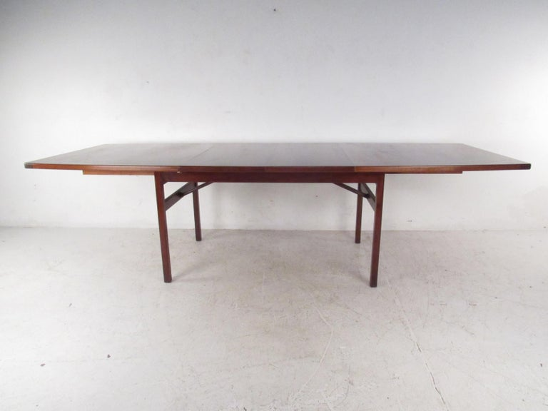 This wonderful vintage modern dining table by Jens Risom Design features a uniquely top that comes with two additional leaves. A well made piece in walnut that easily caters to many guests without sacrificing style. Please confirm item location (NY