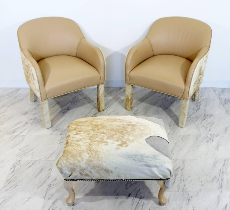 For your consideration is an incredible pair of lounge chairs, made of animal hide and beige leather, and matching ottoman, circa the 1970s. In excellent condition. The dimensions of the chairs are 24