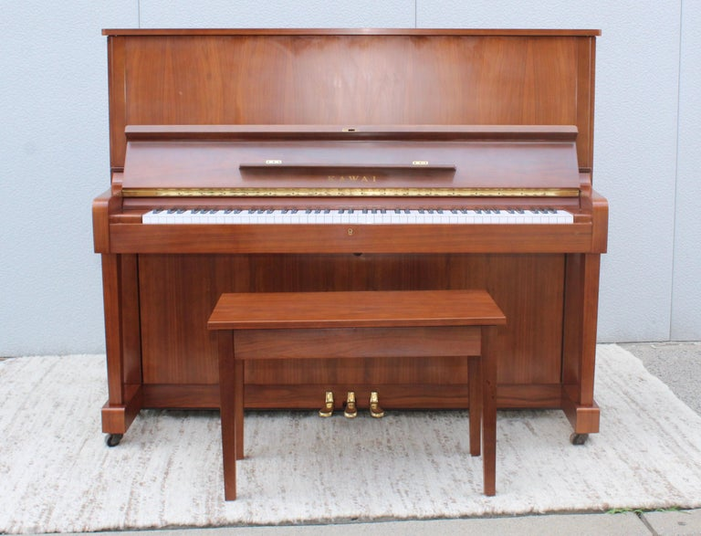 Stunning 1960s modern Kawai upright piano made of walnut with brass hardware model number K1490204. With the original stool and two keys.