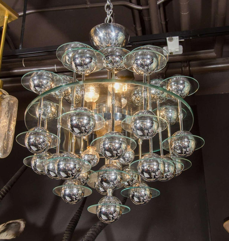 Italian Mid-Century Modern kinetic chandelier with Space Age design. Features central glass disc with suspended spheres of chrome globes. Each orb has a smaller glass disc surrounding it. The spheres hang from chrome rods attached through the center