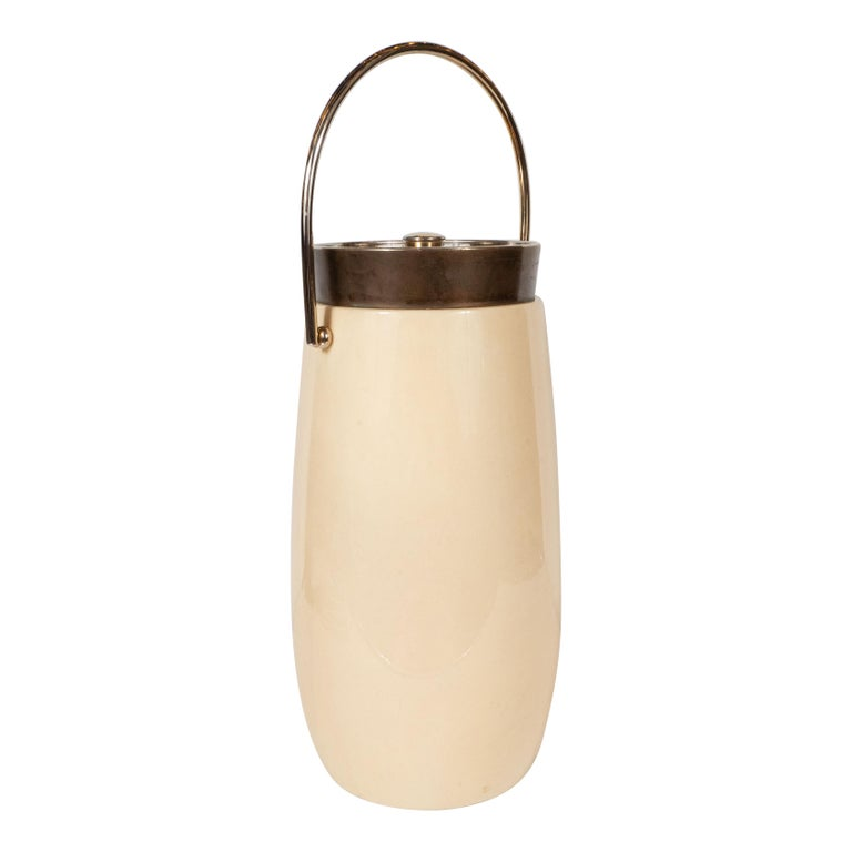 This elegant and dramatic ice bucket was realized by the esteemed Mid-Century Modern designer Aldo Tura in Italy, circa 1970. It features a cylindrical body that tapers to each end with a slightly inset neck in patinated brass with a circular top