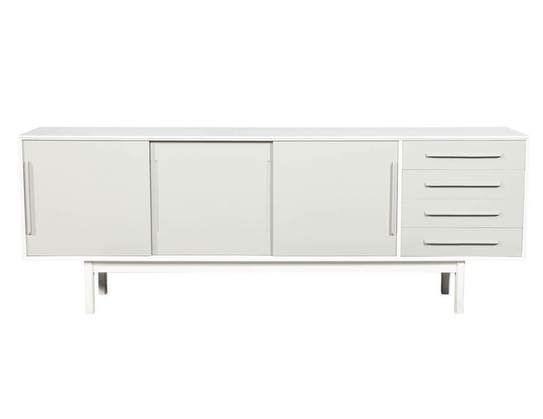 Mid-Century Modern lacquered sideboard media cabinet. Finished in a two-tone designer white and dove grey satin lacquer. This sideboard has clean modern lines and sliding doors and drawers for convenient storage. Restored by the artisans here at