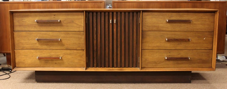 For your consideration is an incredible, ribbed pecan and rosewood bedroom set, including a nine drawer dresser, a four drawer highboy, a pair of tall mirrors,and a headboard, by Lane Altavista, circa 1971. In very good vintage condition. The