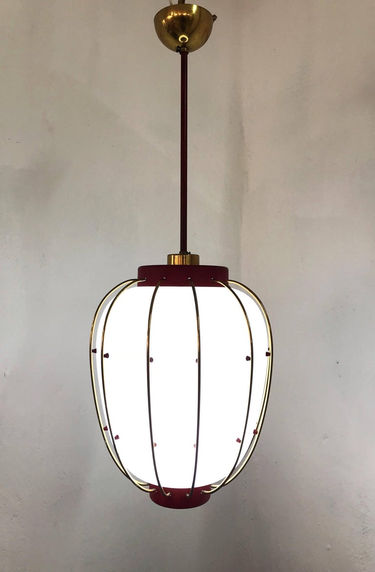 Beautiful pendant light / Lantern in lacquered metal, brass and opaline glass, attributed to Stilnovo and very much in the manner of Angelo Lelii's designs for Arredoluce from the same era. We have 3 available. One in red and two in black.  These