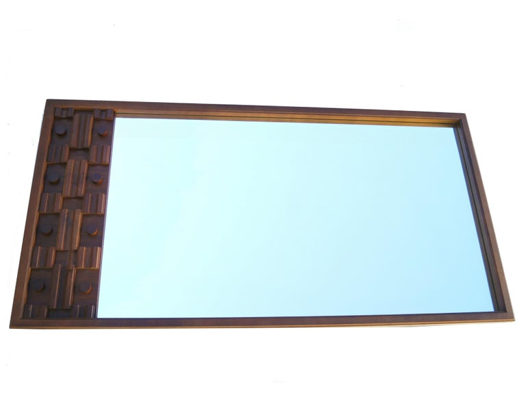 Large 6' Brutalist long sculpted mirror. This is meant to be attached to a dresser or credenza. You will need hardware to attach or heavy hanging hardware. The bottom side is unfinished, as it had been attached to a dresser.
