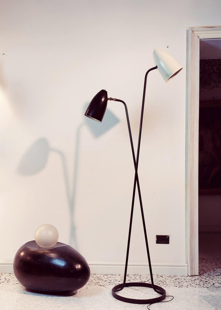 Amazing floor lamp with black and white lacquered reflectors, the white fixed and the black adjustable thanks a beautiful brass joint.
