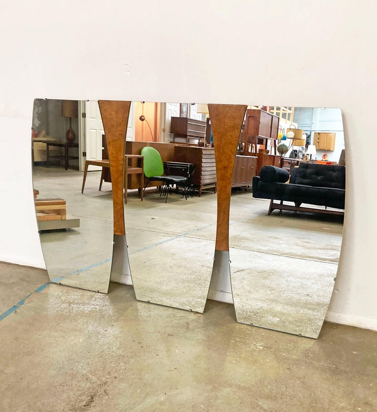 Offered is a cool large Mid-Century Modern mirror (circa 1960s). Features three mirrors attached to a burl wood base. This mirror originally sat on a dresser, but is currently being used as a wall mirror. In good condition, but has one chip on a
