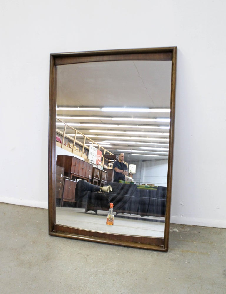 Offered is a vintage Mid-Century Modern wall mirror made by United Furniture. This piece is large and heavy with a walnut frame. It is in good condition shows minor wear including small nicks and scratches on the wood. Does not include a hanger. It
