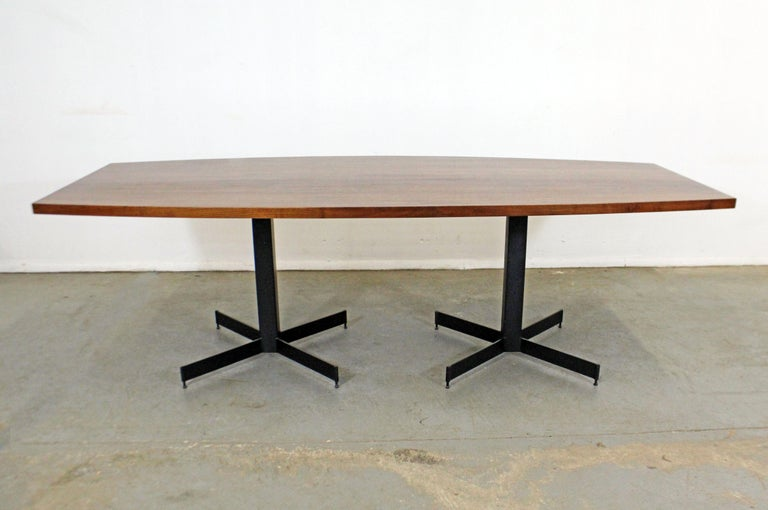 Offered is a large Mid-Century Modern conference/dining table. This table has been recently restored with a refinished walnut 
