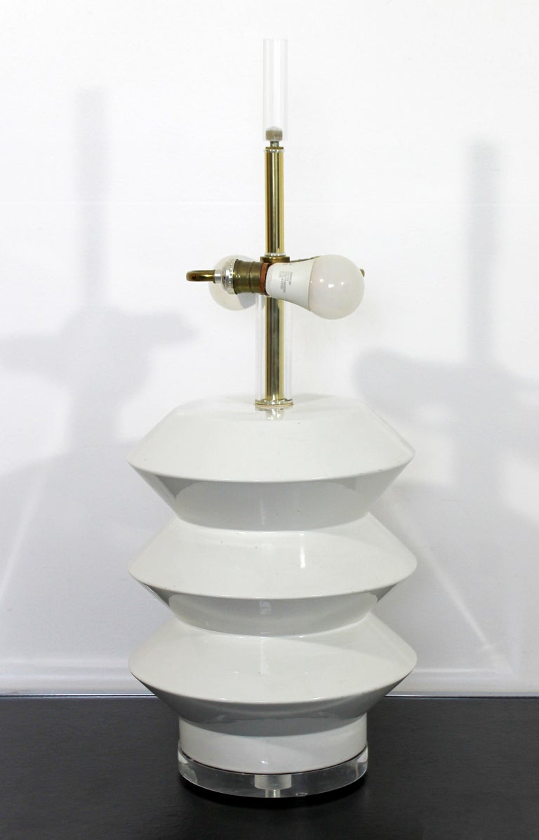 For your consideration is a phenomenal, architectural table lamp, made of white ceramic, brass and Lucite, by Bauer. In very good condition. The dimensions of the lamp are 12