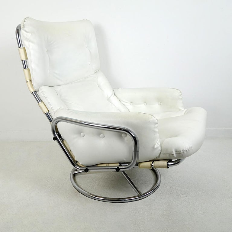 The Tanabe armchair was designed by Martin Visser in the 1960s for 't Spectrum.  It has a steel frame with leather straps on a steel swivel base. The straps are made of off-white colored leather. The seating is white leather.