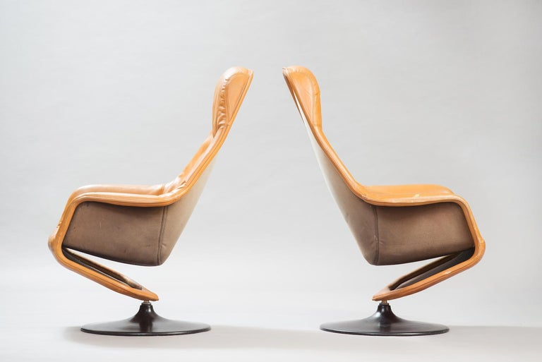 One pair of swivel lounge chairs upholstered in cognac leather in a black lacquered round base.