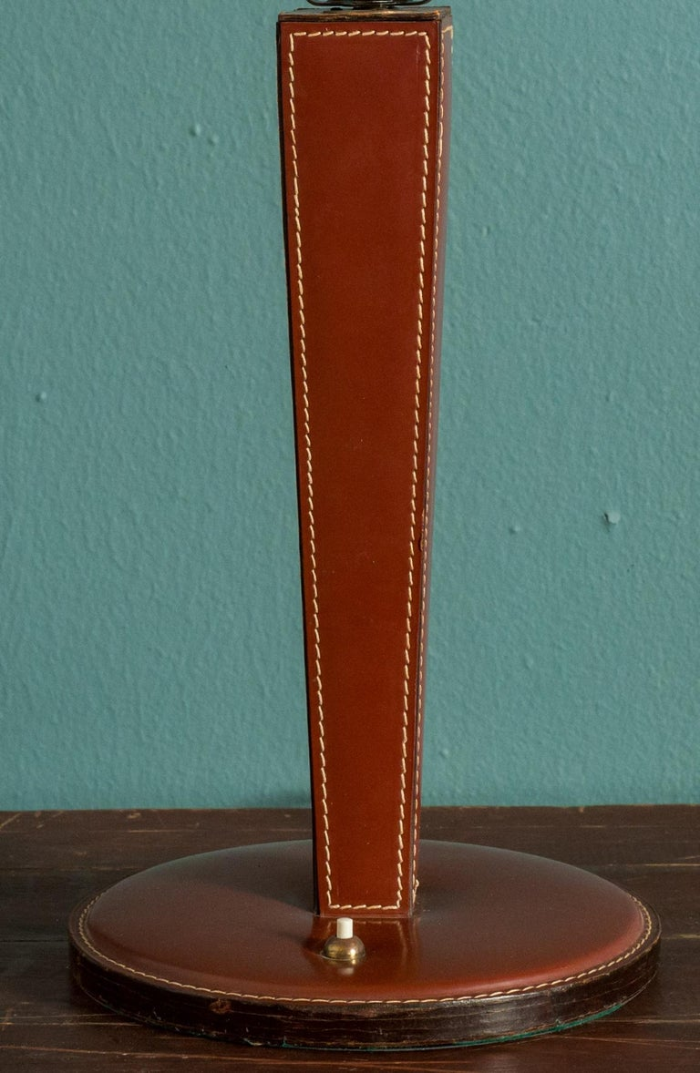 This leather table lamp is in the style of Hermes. It does not carry a mark. It has interesting top-stitching on brown leather. It has been newly wired in the US.