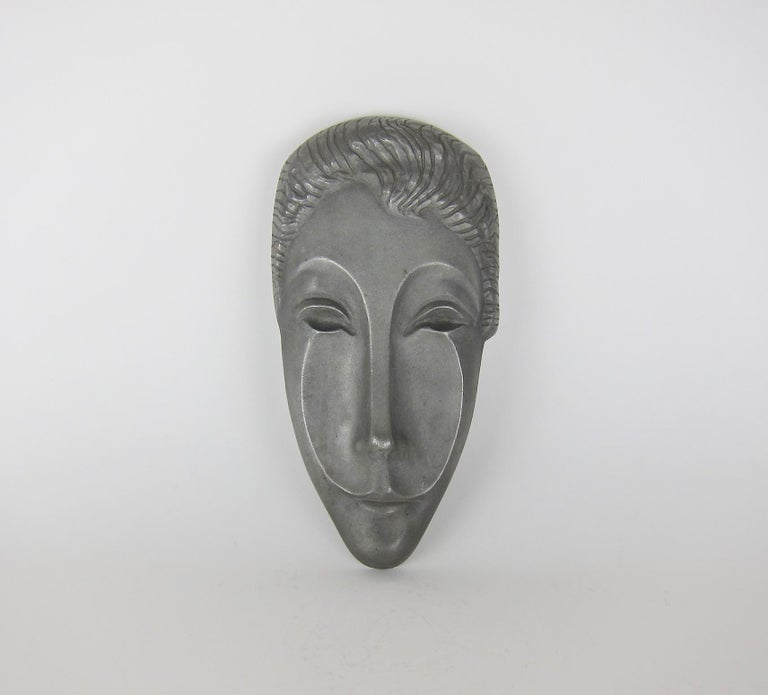 A midcentury mask sculpture of Letitia, the Roman Goddess of joy, gaiety, and happiness, by American sculptor Evaline Clark Sellors (1903-1995). The elongated and abstracted mask of cast aluminum dates circa 1960 and remains in very good condition