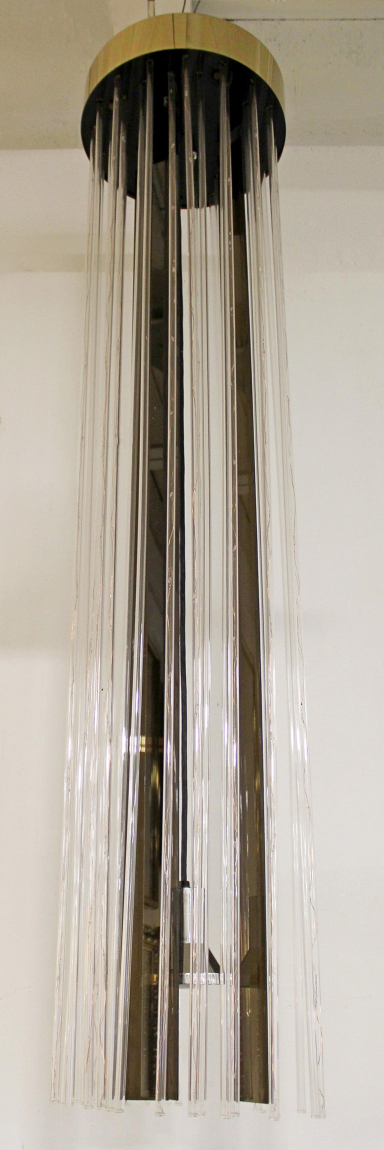 For your consideration is an absolutely fabulous, long hanging chandelier, made of brass and acrylic, circa the 1960s. In very good vintage condition. The dimensions are 16