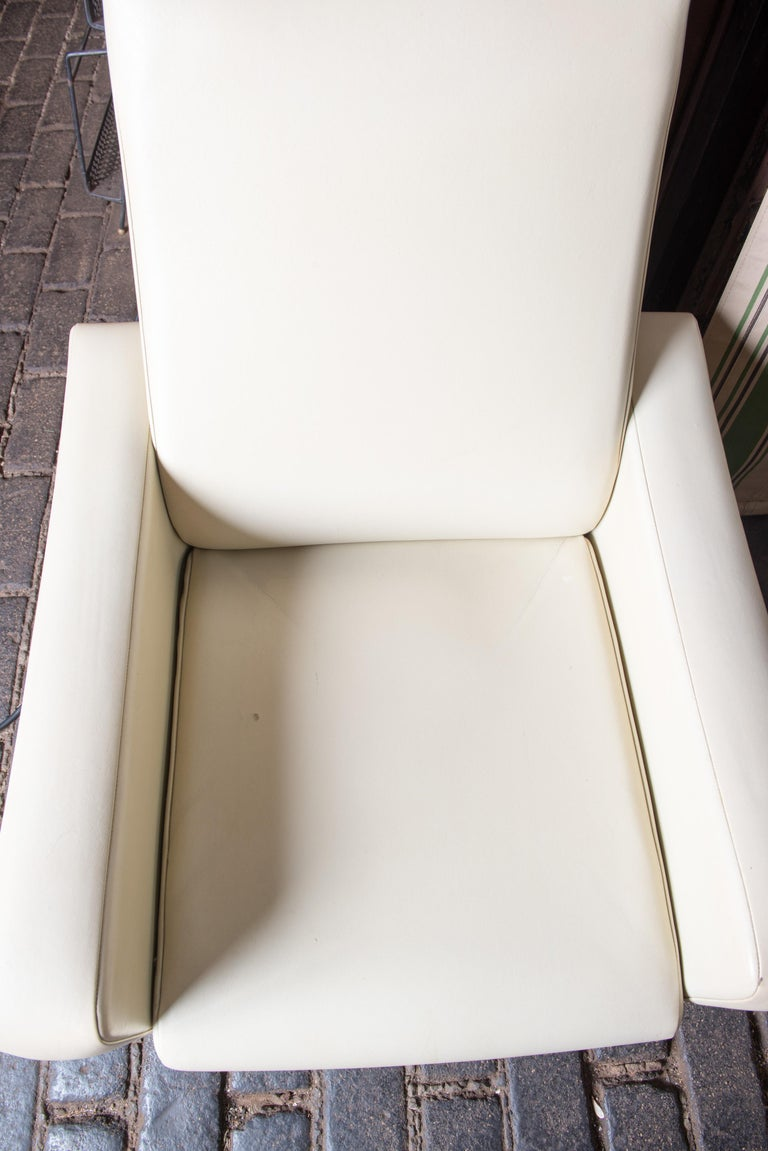 Mid-Century Modern white vinyl chair with metal legs. Nice proportions and style. Small round hole on the outside of right arm. Re-upholstery is a good idea.