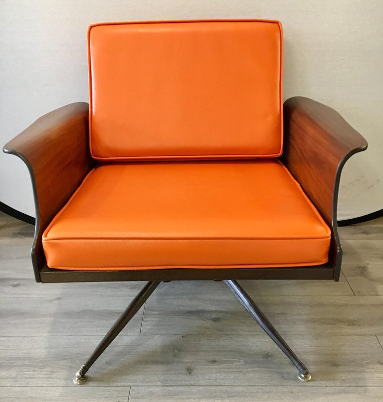 Coveted 1960s original lounge chair redone in a orange pebbled leather that looks gorgeous. Features many Danish accents including the winged arm and streamlined legs. This chair does not swivel.