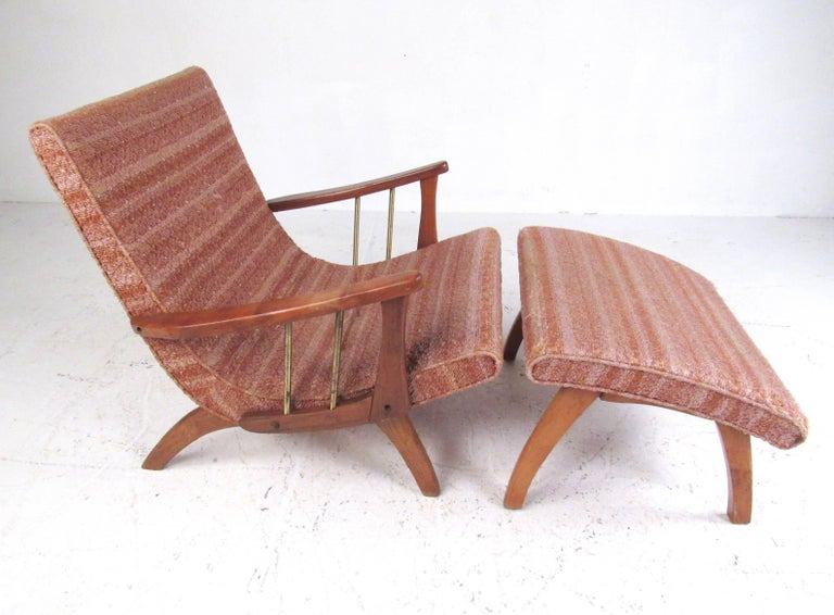 This stylish midcentury lounge chair features sculpted hardwood frame with brass post details and vintage fabric. Stunning retro modern design includes angled legs and seat design, covered in vintage patterned fabric. Ideal seating option for living