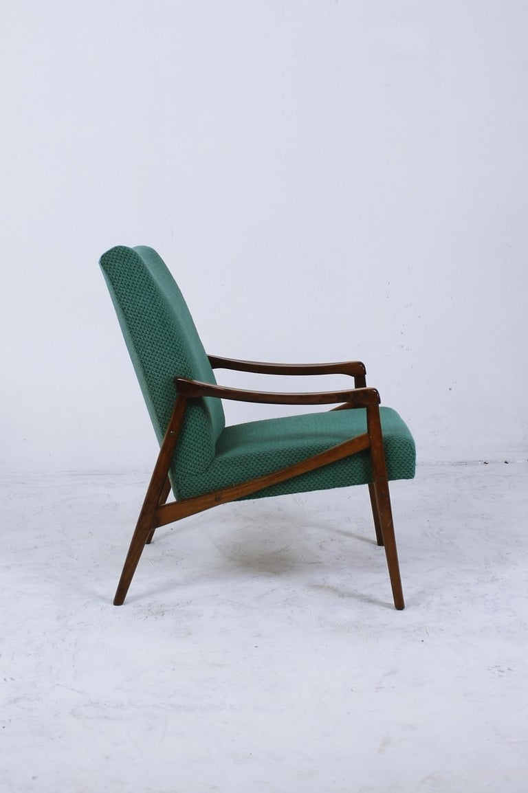 Stylish and elegant midcentury armchair by Interier Praha, produced in 1960s. Original upholstery in good condition with only minor wear. Beautiful stained beech wood frame with interesting details and strong construction.