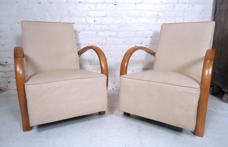 Elegant pair of vintage modern lounge chairs features stylish design and contemporary fabric. Comfortable seats make a unique addition to home or business seating arrangement. 