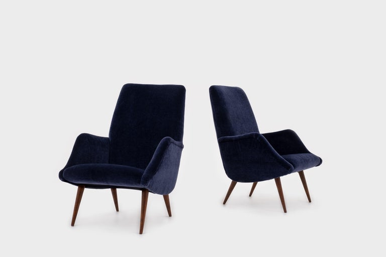Beautiful pair of '806' armchairs by Carlo de Carli for Cassina, Italy, 1955. Elegant curved shape with nice distinctive sharp tapered Italian walnut wooden legs. The chairs are fully reconditioned and are upholstered in a high quality night blue