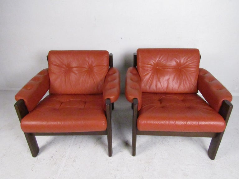 Nice pair of midcentury lounge chairs with tufted upholstery. Sturdily built frames with a dark finish applied, with the seating and rests covered in a vintage blood-orange leather upholstery. The leather covering the seats, backrests, and even the