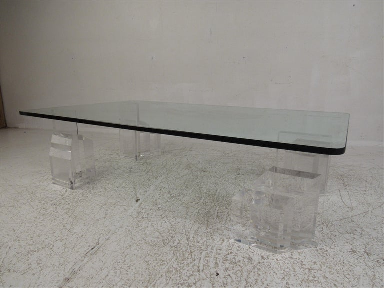 This stunning vintage modern coffee table boasts a large rectangular glass top with a light tint of green. An unusual design with four individual Lucite pieces. An elegant graduated design with beveled edges makes this base stand out from the rest.