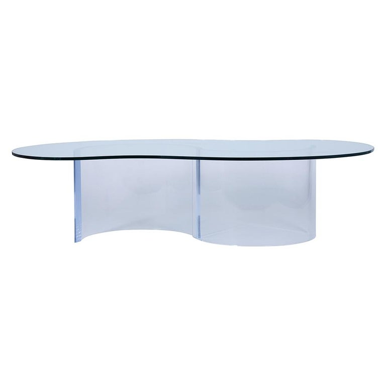 A fabulous midcentury-style cocktail table crafted from Lucite and clear glass. This coffee table features a unique two-piece waveform Lucite base topped with a kidney shape clear temper glass top with a flat polished. The beautiful table makes for