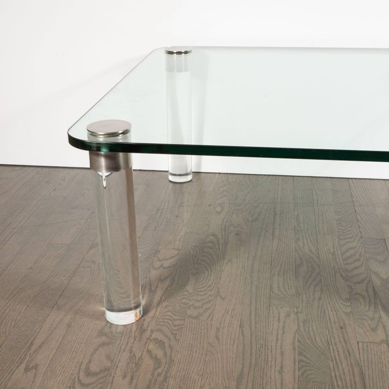 This refined glass and Lucite cocktail table was realized in the United States, circa 1970. Designed by Leon Rosen the founder of the esteemed Pace collection, circa 1970, this stunning table features cylindrical Lucite feet topped with brushed