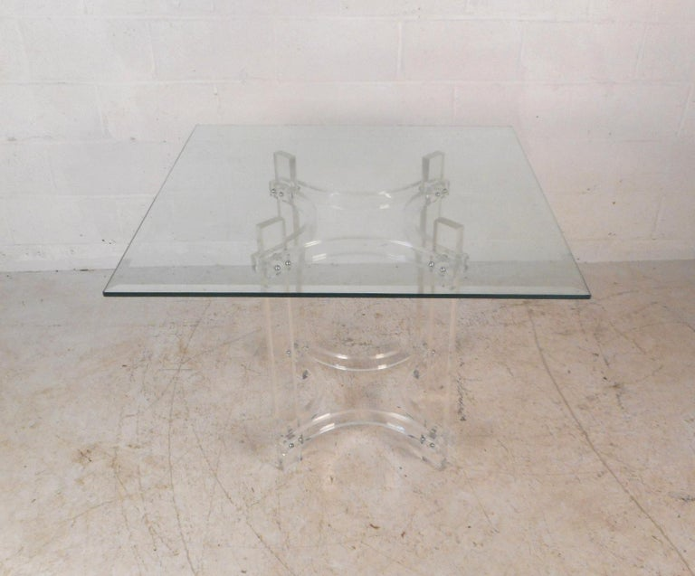 This gorgeous vintage modern dining set includes a Lucite base table with a glass top and four dining chairs. The stylish dining table has a base made entirely of Lucite and a thick square glass top ensuring plenty of room for guests. A lovely set
