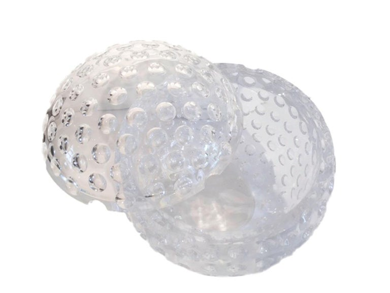 Vintage Lucite ice bucket of spherical form with a pivoting top. The entire surface covered with golf ball-like divots, each of which reflects the others creating an optical effect.