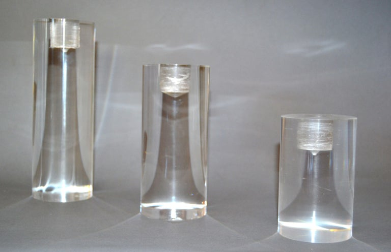 Set of three Mid-Century Modern Lucite candleholders in graduated sizes. Large, 7.38 inches height x 2.5 inches diameter. Medium, 5.63 inches height x 2.5 inches diameter. Small, 4.00 inches height x 2.5 inches diameter. Designed to fit any