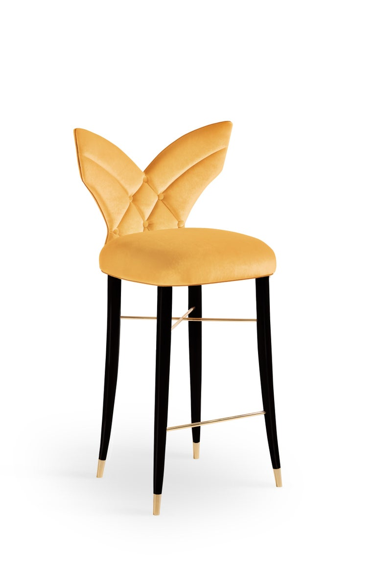 An unusual majestic elegance and sensuality surround the Luna contemporary bar chair. The slender and curved solid walnut wood legs with the signature brass details complete the surprising and memorable wing-shaped backrest. The extreme comfort of