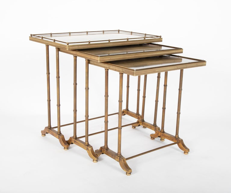 A set of three all brass nesting tables with beautiful patina. The largest with a gallery top, all with round legs resting on bracket feet supported by hexagonal stretchers. A beautiful design combining a modern take on the traditional with an