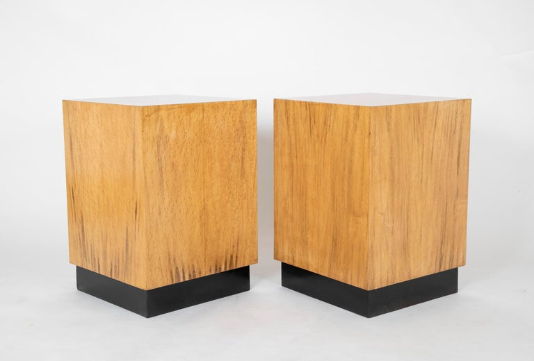 Great looking pair of mid 20th century cube-form side tables covered in birds-eyes maple veneer, on recessed black bases. These make very distinctive end tables or pedestals. At 25.5 inches high, they are perfect for either side of living room