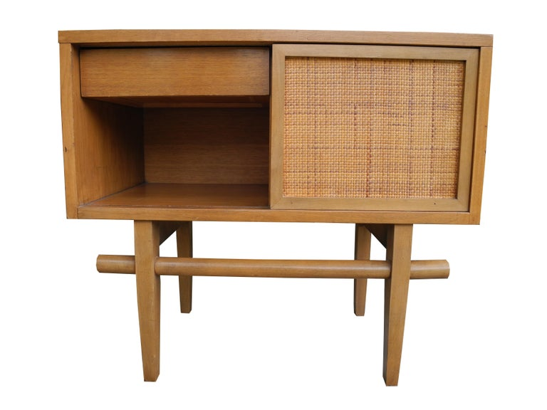 This Asian influenced vintage modern design single nightstand has a rattan sliding door that reveals or hides a drawer or cubby.