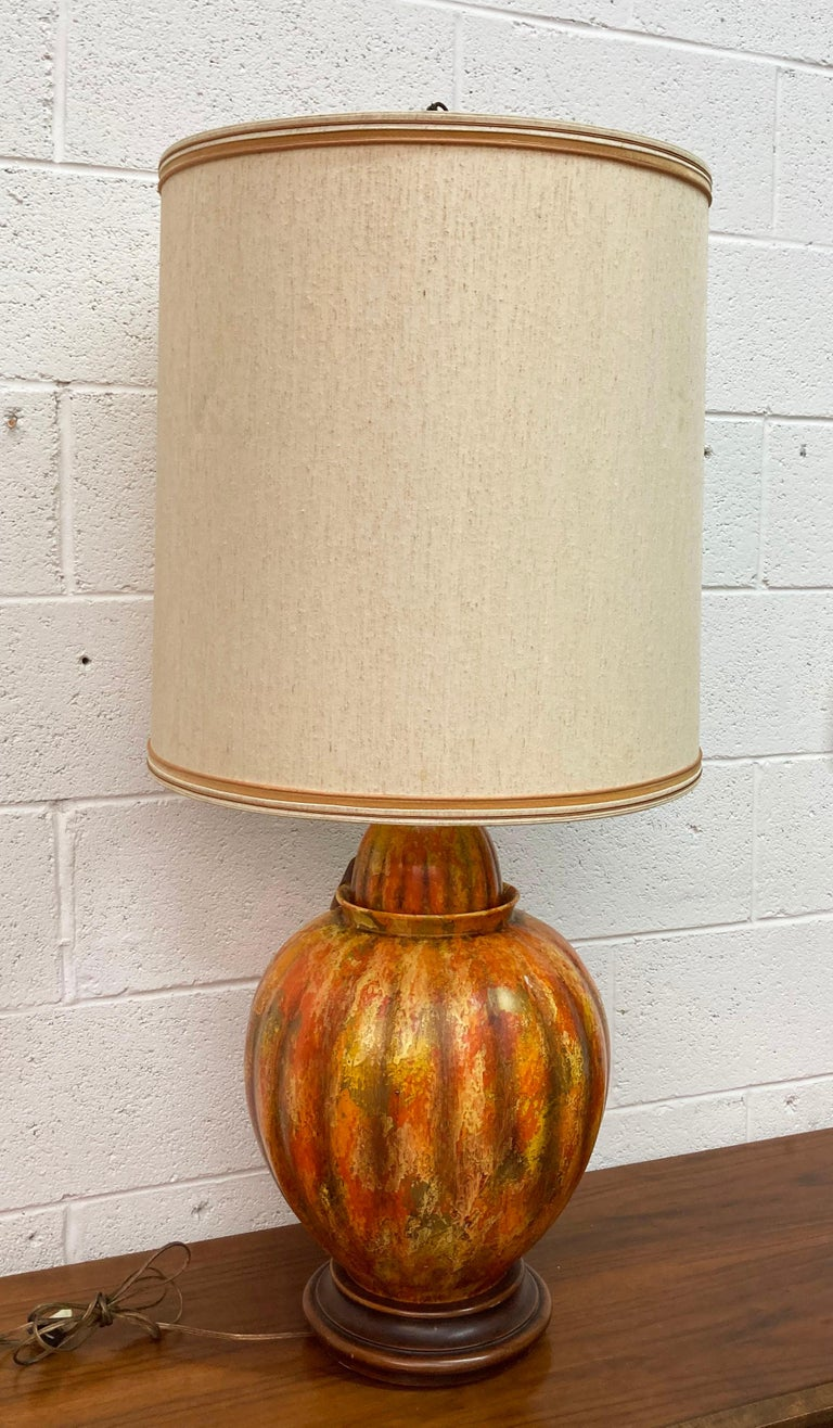 Offered is a large vintage Mid-Century Modern table lamp by Marbro. This unique lamp features a painted ceramic or porcelain body that sits on a wooden base. Also includes a unique finial and double bulbs with a pull chain. It has been tested and